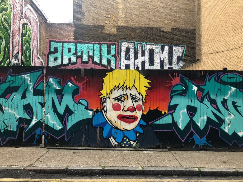 Brick Lane Graffiti Street Art – Boris Johnson UK Prime Minister Clown amid Covid 19 Pandemic NHS crisis